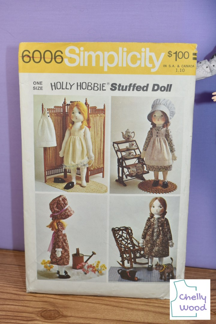 """Here we see a close-up image of Simplicity Craft Pattern #6006. This pattern, marked with a copyright from 1973, shows the soft-bodied Holly Hobby dolls in four different outfits: undergarments (including bloomers and a slip), a white floral dress with a white dotted Swiss pinafore and blue bonnet, a rust-colored floral dress with a ribbon that ties around the middle of the doll and a matching bonnet with ribbon, and a brown floral dress with lace trim. If you'd like to learn more about this pattern and its history, please visit ChellyWood.com and click on """"Old Patterns from Chelly's Collection"""" under the """"categories"""" feature."""