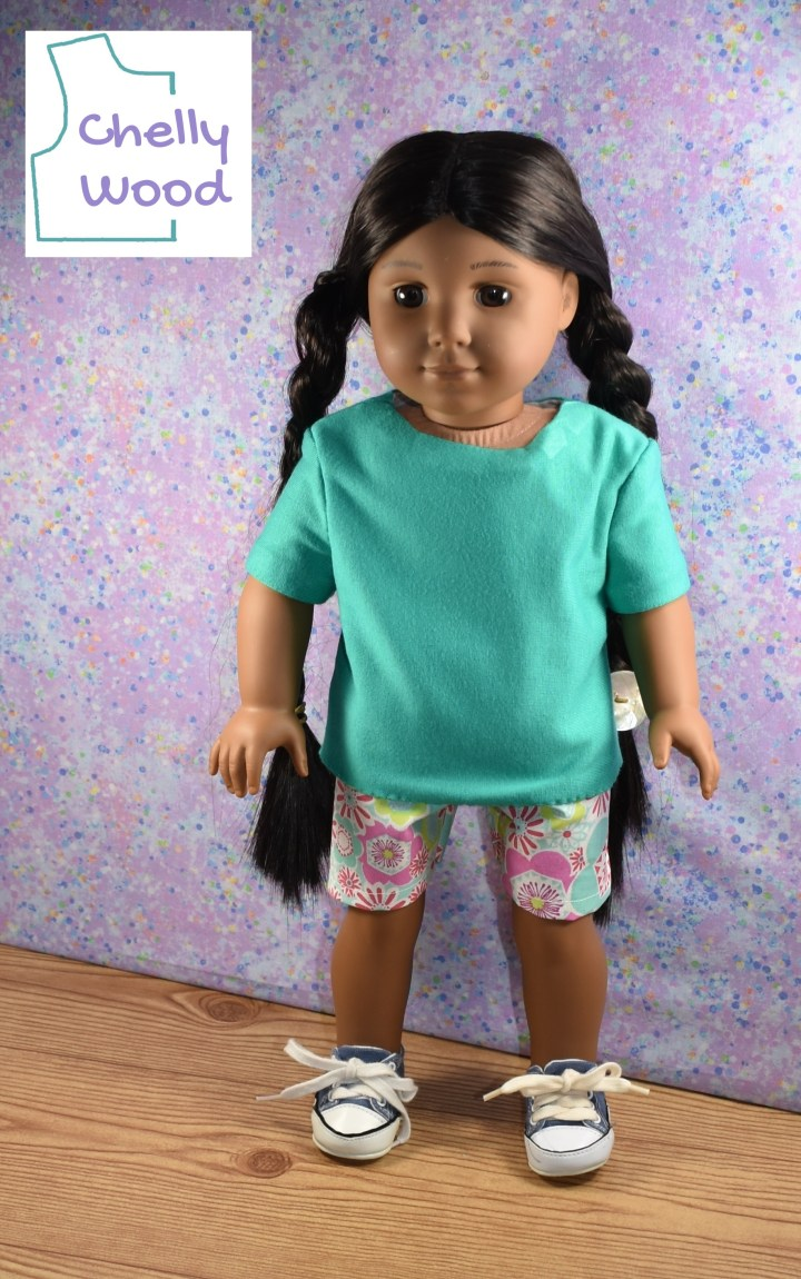 This photo shows the Kaya doll from the American Girl dolls collection wearing a turquoise green jersey fabric tee shirt with colorful pink and turquoise cotton shorts.