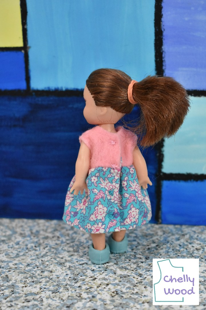 Here we see a Kelly doll from the back. Her pony tail is prominent. She wears a miniature handmade dress with tiny snaps down the back. We can't really see the snaps in this photo; rather, they appear to be hidden under the felt bodice and cotton skirt. The only evidence that demonstrates there are snaps beneath the fabric is a tiny little notch of thread at the point where each snap is hidden behind the folds of the fabric. We're reminded that the patterns and instructions for making this dress can be found at ChellyWood.com by the presence of a watermark in the lower right corner of the photo.