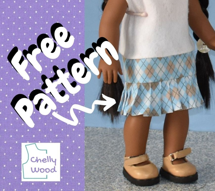 """The image shows a purple dotted swiss fabric background in a square shape. The photo within that shape shows an American Girl doll with brown complexion from the torso down to her feet. She wears a felt shirt, a blue plaid skirt with a ruffle that has been sewn in the form of knife pleats, and a pair of patent leather tan Mary Jane shoes. The overlay says, """"free pattern"""" with an arrow pointing to the cotton skirt with pleats. There's also a watermark on the image, reminding us to visit Chelly Wood dot com for all our free printable PDF sewing patterns for making doll clothes to fit dolls of many shapes and all different sizes."""