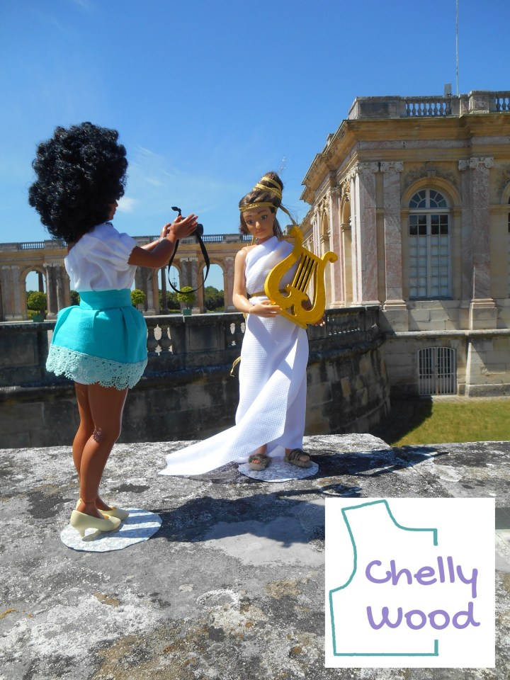 Here we see the Lammily Photographer doll taking a photo of the Lammily Traveler doll. The Traveler doll wears a toga of sorts and holds a gold lyre. They stand before one of the outbuildings on the grounds of the Palace of Versailles near Paris, France. The watermark reminds us that Chelly Wood dot com offers free printable sewing patterns for making doll clothes to fit dolls of many shapes and all different sizes.