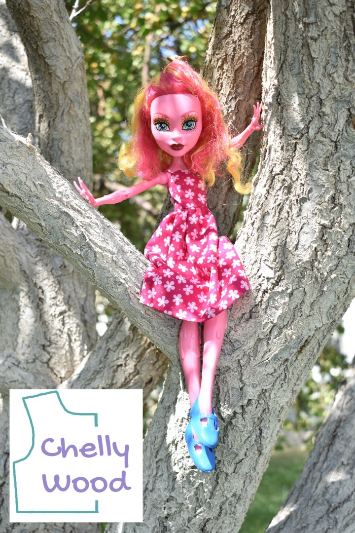 The image shows a 17 inch Gooliope Jellington doll from the Freak du Chic Monster High collection. She's seated between the branches of an apricot tree. She wears a hot pink sun dress with tiny pale pink and white flowers. She also wears turquoise blue Mary Jane style or patent leather style rubber shoes. Her feet are crossed at the ankles, like she's comfortably seated in the tree. One arm rests on a tree branch that reaches vertically upward. The other hand rests on a branch that is at more of a 45 degree angle. The leaves cast shadows on her pale pink skin and pink hair with streaks of golden hair throughout. Green leaves form a pretty summer background color to the whole photograph. In the lower left corner, the watermark reminds us to visit Chelly Wood dot com for free printable sewing patterns to make this dress and many other doll clothes.