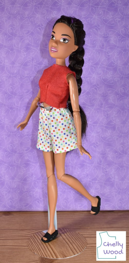 """The image shows a Mattel Barbie Dreamtopia Endless Hair Kingdom 17"""" Doll wearing handmade clothes that include a red felt crop top (sleeveless) and a pair of polka dot casual shorts with an elastic waist. The watermark on this image says """"ChellyWood"""" which reminds us to visit ChellyWood.com for free printable PDF sewing patterns for making this and other doll clothes outfits for dolls of many shapes and all different sizes. If you'd like to find free patterns and sewing tutorials for making these doll clothes (the shirt and shorts clothing pictured here) to fit your 17 inch Barbie Dreamtopia Endless Hair Kingdom doll, please click on the link in the caption."""