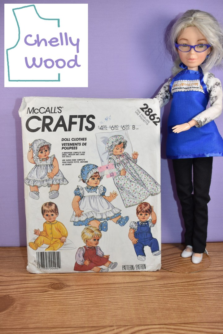 In this photograph, the Chelly Wood doll (a Spin Master Liv doll that has been repainted and had its wig dyed to look like the real doll clothing designer and writer Chelly Wood) holds up a copy of the McCall's Crafts baby doll clothes pattern number 2862. There's also a logo for the ChellyWood.com website, where you can find lots of free printable PDF sewing patterns for making doll clothes to fit dolls of many shapes and all different sizes. This image comes from a blog post that explains how to make dolly pajamas or PJ's and/or slippers from everyday patterns.