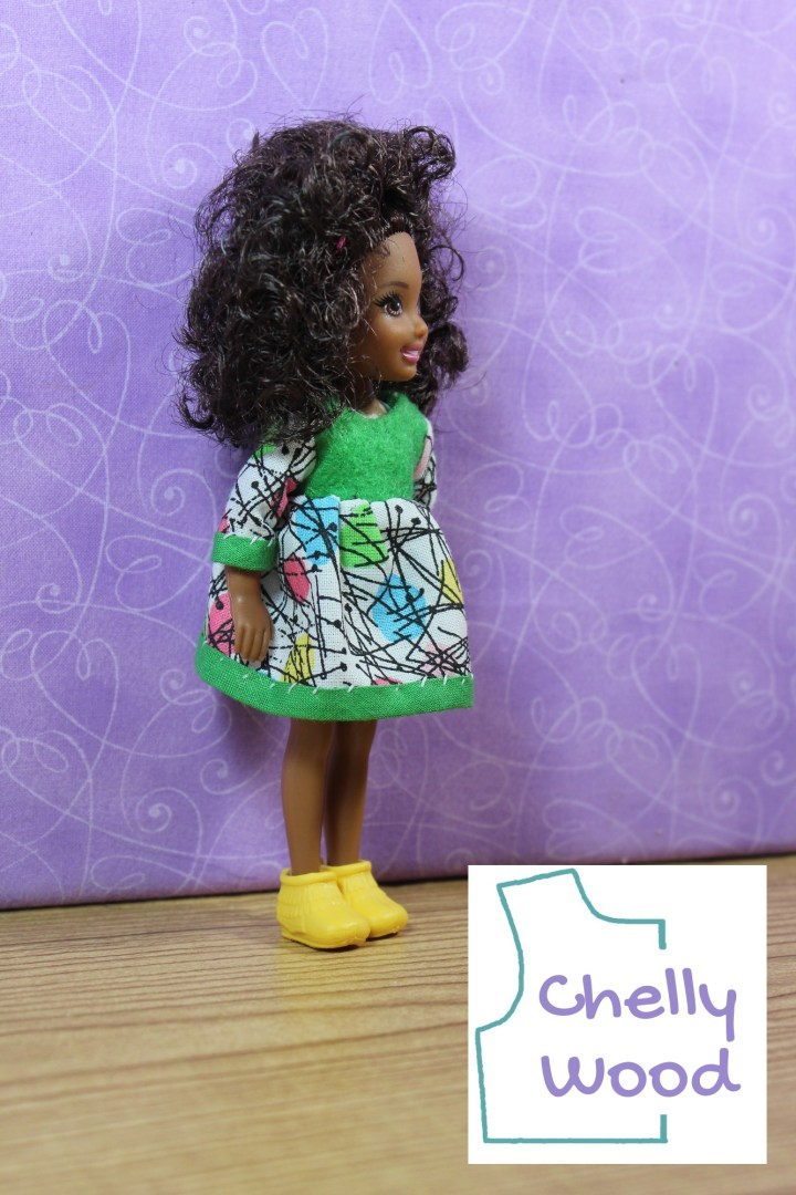 A five and a half inch or 13.5 cm Chelsea doll stands in front of a purple backdrop. Her face is in profile. She has a chocolate complexion with wild and wonderful black curly hair. She wears a brightly colored dress with three quarter length sleeves. The dress uses green craft felt for the bodice and green bias tape as a trim at the hem and sleeve cuffs. The sleeves and skirt of the dress are made of white cotton fabric decorated with colorful ovals and black slash marks. The watermark reminds us that free printable sewing patterns for making this dress are found at the Chelly Wood dot com website.