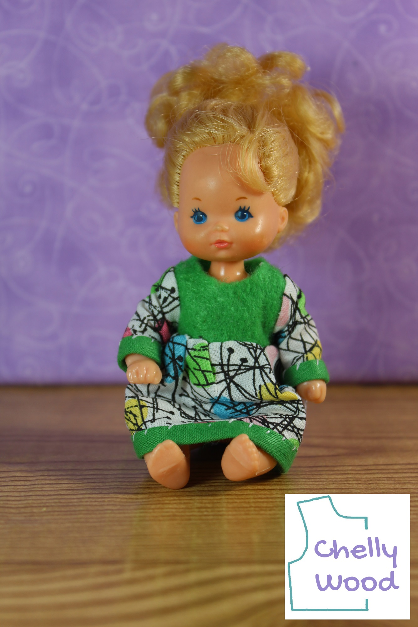 This image shows a Heart Family baby doll modeling a handmade green and white and multicolored dress. Patterns for making this dress with its long sleeves and bias tape trim can be found at Chelly Wood dot com under the 4 inch doll clothes pattern collection. This image of the Heart Family doll shows the little baby looking slightly to her right with her pale blue eyes. She's seated on a wooden floor with a purple backdrop behind her.