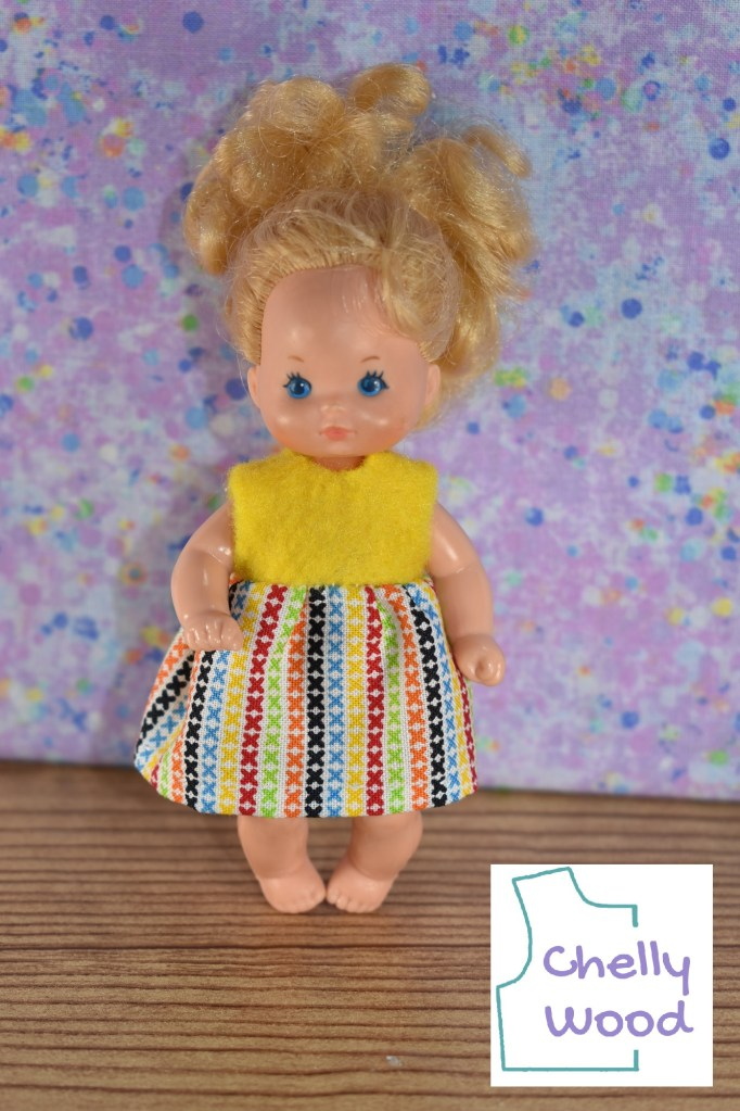 The camera has zoomed in so we get a very close look at a miniature dress which is designed to fit the 4 and a half inch Heart Family baby doll. The image shows a Mattel Heart Family Barbie Baby doll wearing a handmade dress. The dress is made of a yellow felt bodice and a multi-colored cotton skirt that has been gathered and attached at the bottom of the felt bodice. To download and print the free pattern for making this Heart Family baby doll dress, please visit ChellyWood.com and search for the pattern under 4 inch doll clothes.