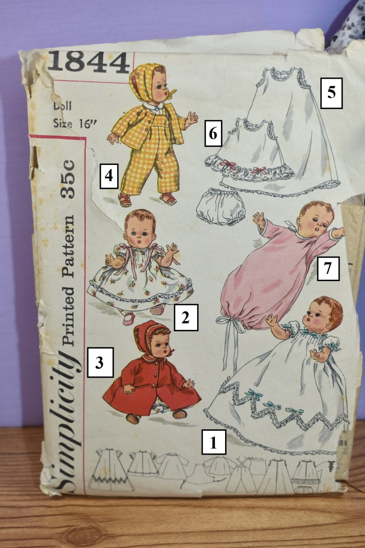 The image shows a close up of the cover of vintage Simplicity doll clothes pattern number 1844 which has a copyright date of 1956. The photograph has been enhanced with enlarged numbers for each view. In View 1, a baby doll wears a baptismal dress trimmed in lace around the hem with a zigzag of lace about four inches above the hem; each zig zag in front is topped with a tiny blue ribbon like the tiny blue ribbons on the ruffled sleeves and collar. In view 2 a little white dress made of rose-printed fabric is trimmed inn lace about an inch above the skirt's hem, and above each puffy sleeve, we see a pink ribbon tied in a bow. In view 3 a red coat has a little round collar trimmed in rickrack to match the rickrack trim around the matching red bonnet. In view 4 the doll wears a white shirt, a pair of yellow gingham overalls, a matching gingham jacket, and a matching yellow gingham bonnet. In view 5, we see a slip trimmed in lace around the hem, collar, and sleeves. Beside it, a smaller dress or slip has a similar lace around the collar and sleeves, but the hem is trimmed in 1 inch eyelet and tiny pink ribbons. These two slips also come with unadorned white underpants. In view 7, we see a pink baby bunting which is trimmed with ribbon or bias tape (or both).
