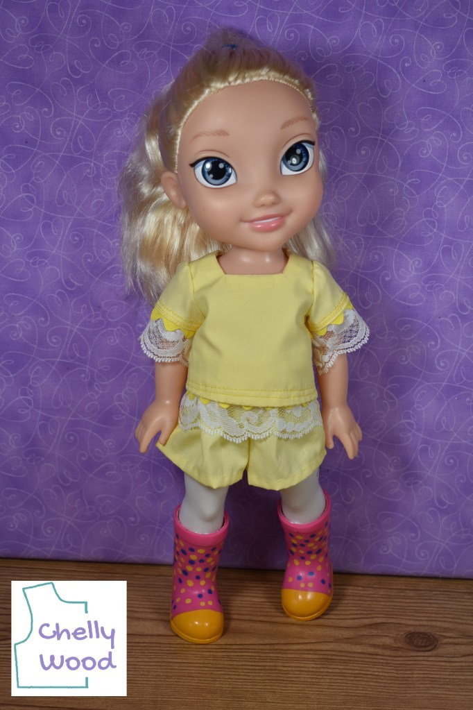 In this photo, a Disney Princess Toddler doll with platinum blond hair pulled back into a pony tail models a handmade shirt and shorts. The shirt is made of yellow cotton with lace edging the sleeves and the bottom of the shirt. The sleeves also have a darker yellow colored rickrack trim around the sleeves' hem. The shirt's neckline is a square shape. The shorts have an elastic waist that isn't seen in the photo. Under this outfit, the Elsa doll wears a pair of rubber rain boots that are pink with yellow toes and yellow-and-blue spots over the pink rubber of the main part of the boots. If you're familiar with Wellie Wisher dolls, you'll recognize these boots are Wellie Wisher doll boots. The watermark on this photo reminds us to go to ChellyWood.com for free printable PDF sewing patterns and tutorial videos showing us how to make these doll clothes.