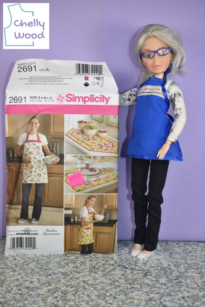 In this photo, the Chelly Wood doll (a Spin Master Liv doll) wears a tiny Barbie-sized apron (made using a free pattern from ChellyWood.com), while holding up Simplicity Apron Pattern 2691 that includes a table runner pattern and a placemat pattern.