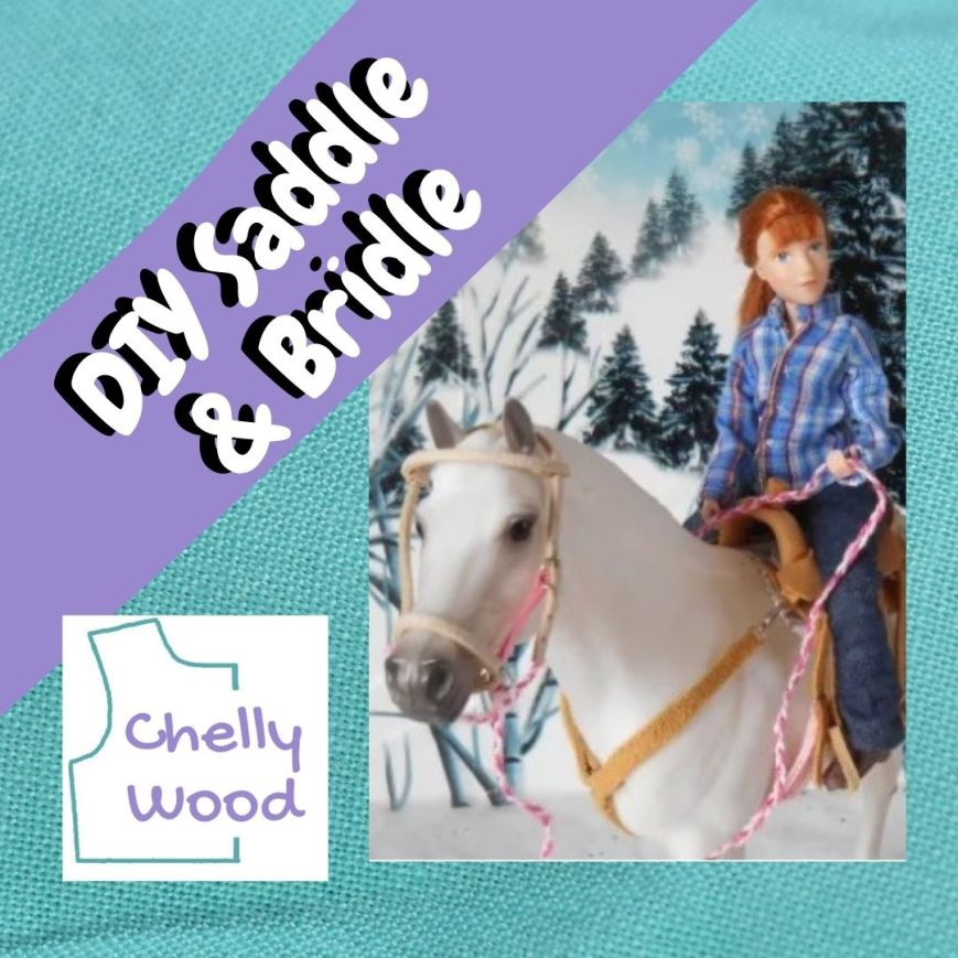 """Here we see the Breyer Rider called """"Veterinarian Laura"""" riding """"Snowball"""" in a winter scene. She holds a lead rope and her horse wears a tan bridle with a tan saddle. The overlay says, """"DIY saddle and bridle"""" and reminds us that this image comes from Chelly Wood dot com (using the watermark image for that website)."""