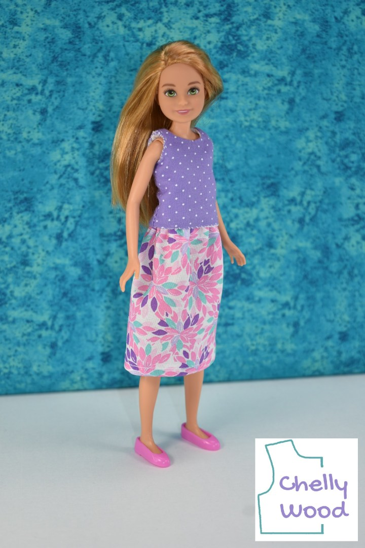 A stacie doll stands at a slight angle. She wears a purple cotton tank top made of dotted Swiss style fabric and a leafy-printed cotton skirt. The skirt is long enough to cover the doll's knees. She also wears pink plastic shoes. The watermark reminds us that the free printable PDF sewing patterns and tutorial videos for making this outfit can be found at ChellyWood.com (the website associated with the Chelly Wood logo).