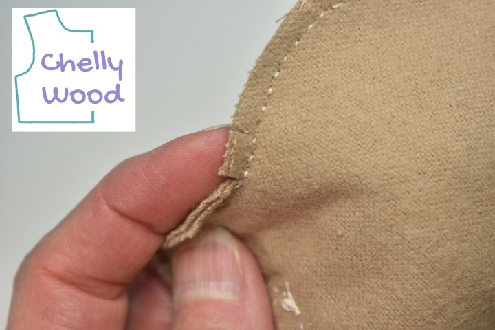 """In this close-up photograph, Chelly Wood's fingers press against the seam of the plush bear, showing that she has clipped this seam very close to the stitching without cutting through the stitches. The watermark says """"Chelly Wood."""""""