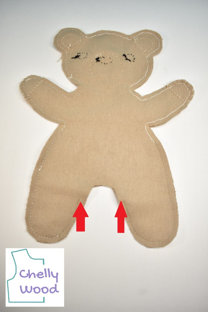 """In this image, a plus bear lay on a white table. We see it inside-out, with the seams exposed. The seams go all the way around the edges of the 2-dimensional bear, but they stop just shy of the crotch area. Red arrows point to where the seams stop upon nearing the crotch, to allow a place for inverting. The watermark says, """"Chelly Wood."""""""