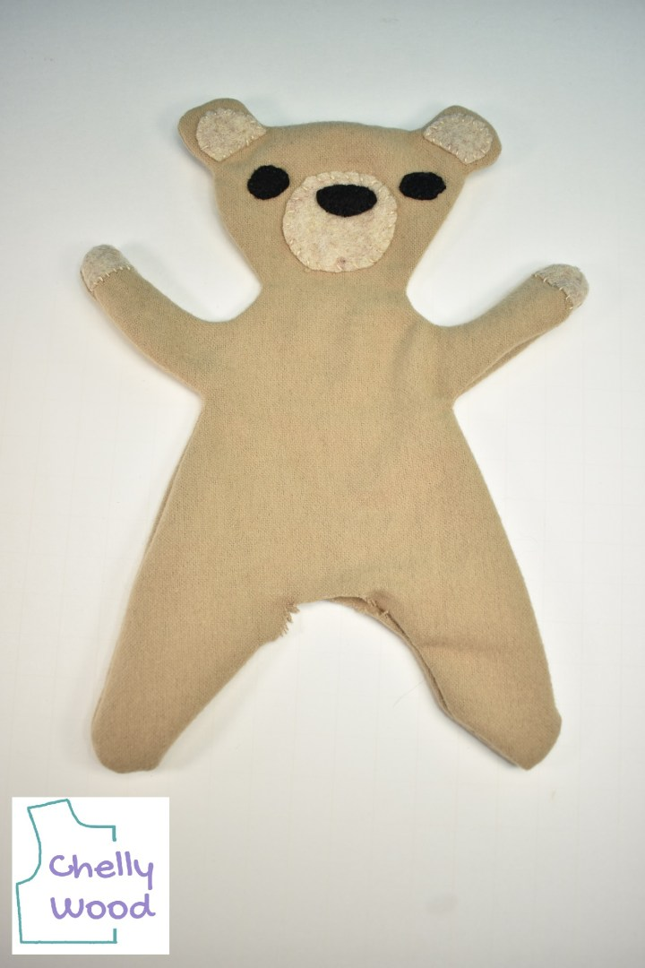 """Here we see a plush bear toy that has been hand sewn and inverted, but it lacks stuffing. The watermark says, """"Chelly Wood."""""""
