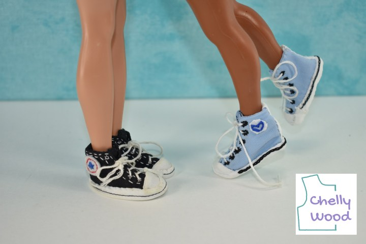 In this photo, a Ken doll wears a pair of black Converse style sneakers, while African American Lammily doll wears a pair of powder blue Converse style sneakers. The Ken doll appears to be standing with his feet together, quite still, while the Lammily doll appears to be leaning in with one foot cocked in the air while the other foot lifts up on tiptoes. Although we don't see the dolls' faces (we can only see them from the knees down), the photo gives the impression that Lammily has leaned in for a kiss! The watermark reminds us to go to Chelly Wood dot com for the free printable PDF sewing patterns and tutorial videos for making these doll Converse tennis shoes or trainers.