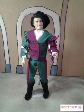 """Visit ChellyWood.com for free printable sewing patterns for dolls of many shapes and sizes. Image shows Ken doll in charming Renaissance cosplay gear/clothes including bi-colored pants, renaissance doublet, ribbon-tied sleeves, fancy shirt, felt boots, and muffin cap. Watermark says, """"Chelly Wood dot com for free, printable sewing patterns to fit dolls of many shapes and sizes."""""""