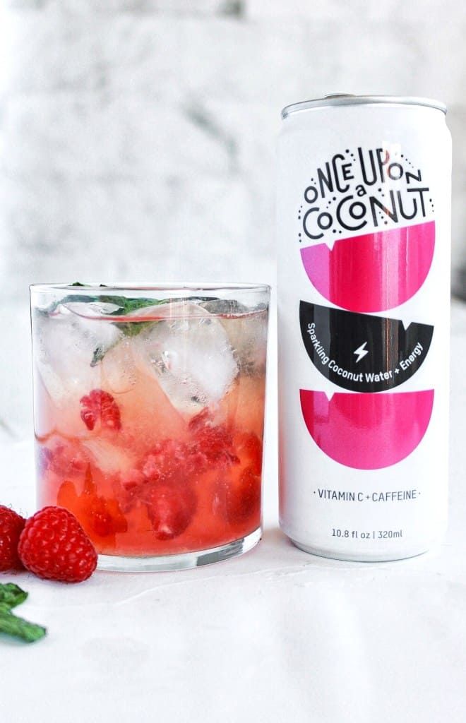 Lemon Raspberry Mojito in a glass with raspberries next and ice within the glass.