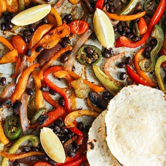 Vegan Black Bean Sheet Pan Tacos on the sheet pan with tortilla on top.