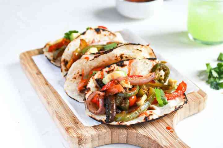 Vegan Black Bean Sheet Pan Tacos up close with a side view to see all veggies inside.
