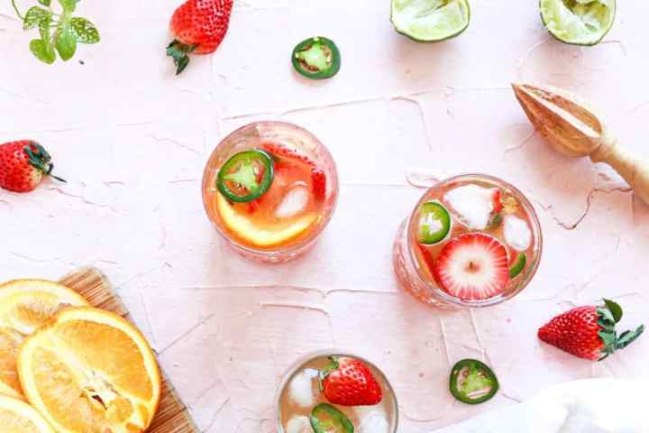 The Margaritas in glasses with garnishes rims. There are fruit garnishes surrounding it and oranges on cutting board