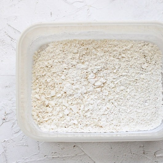 Coconut crust mixture (wet powder) in a square tipper bowl container