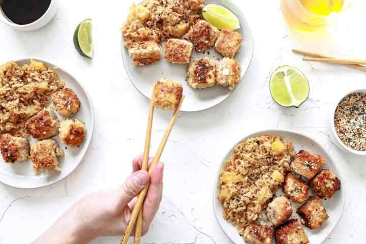Coconut crusted tofu with sesame seeds plated on three plates with pineapple rice next to it. There are also chopsticks with one tofu piece being pulled away and clear beverages within the scene