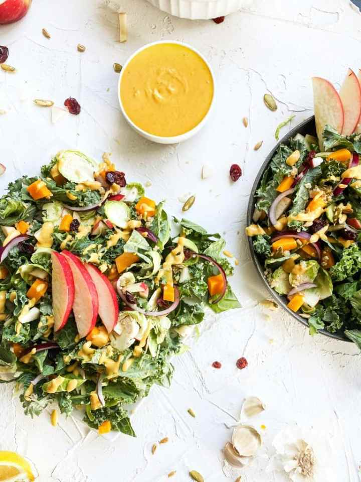Pumpkin Tahini Autumn Salad with bowl of salad dressing next to it