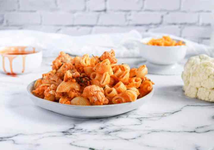 Buffalo Cauliflower Vegan Mac and Cheese in a bowl with chives on top