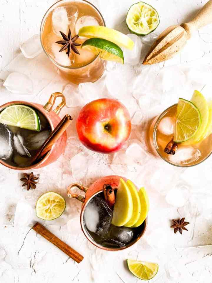 Overhead shot of Apple Cider Moscow Mule with ice, cinn sticks, lime wedges and apple slices