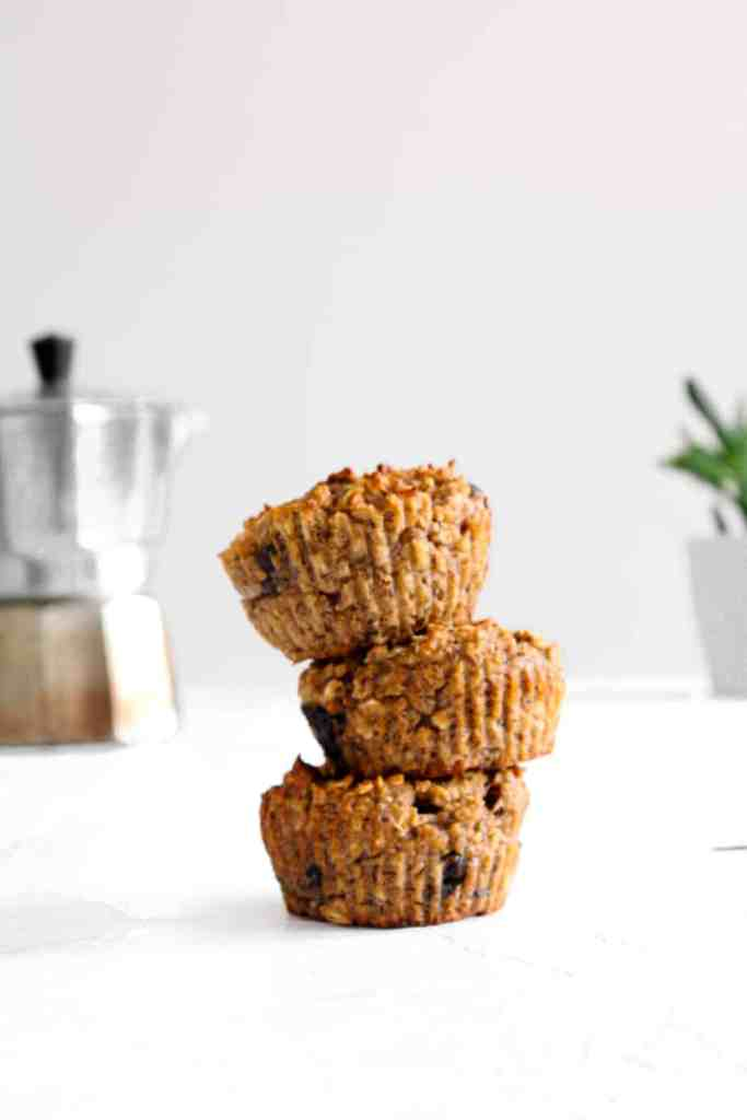 Chocolate Banana Protein Muffin in a stack (3) with a coffee perker and plant in back