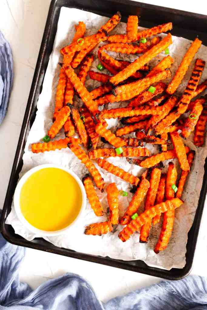 Sweet Potato Fries Cooked on top of parchment paper on a baking tray
