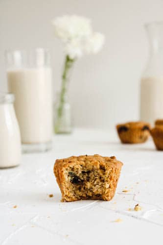 Vegan Blueberry Lemon Muffin (one) with a bite taken out of it so you can see the soft inside on a white counter with white flowers, muffins and milk in the back