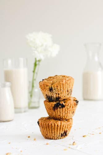 Vegan Blueberry Lemon Muffins stacked in three with a white background with flours, milk and glasses