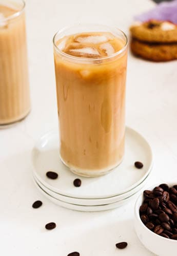 Iced Oat Milk Latte in a glass with coffee beans all around and cookies in back