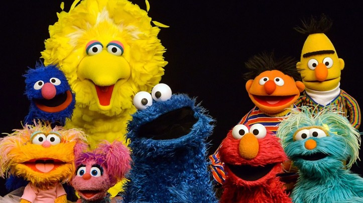 sesame street characters smile in a group