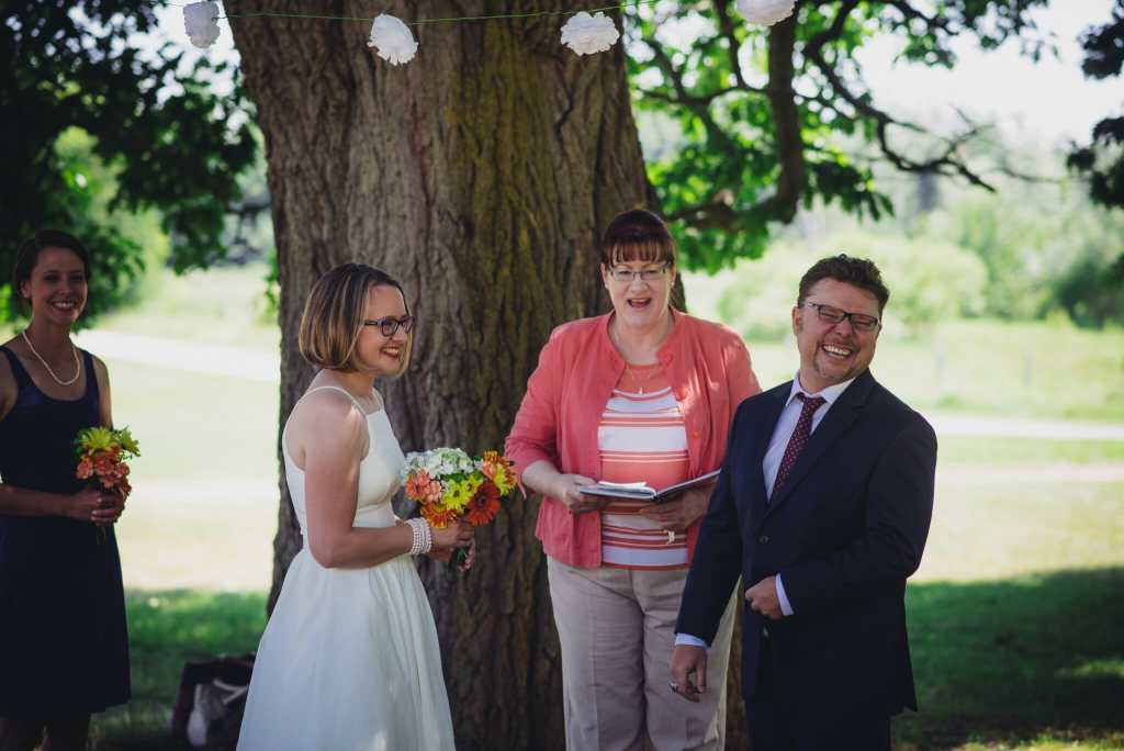 couple laughs during outdoor camp wedding ceremony