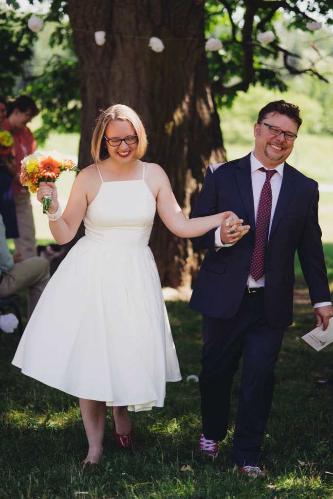 happy newlyweds walk down the aisle as spouses