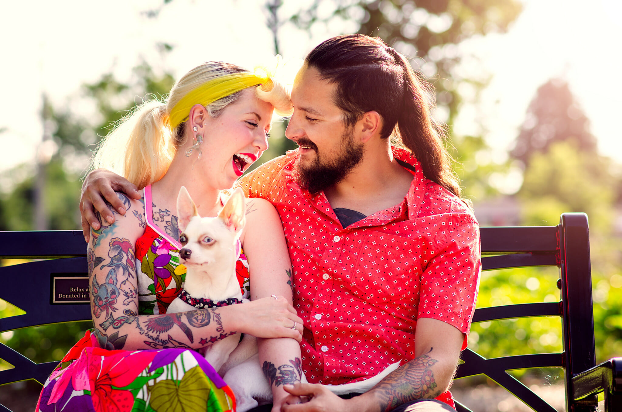 couple laugh on park bench during the summer