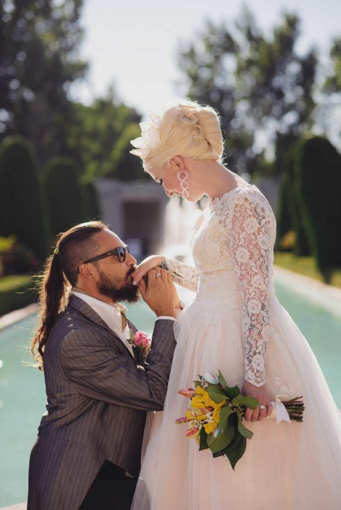 groom kneeling kisses brides hand
