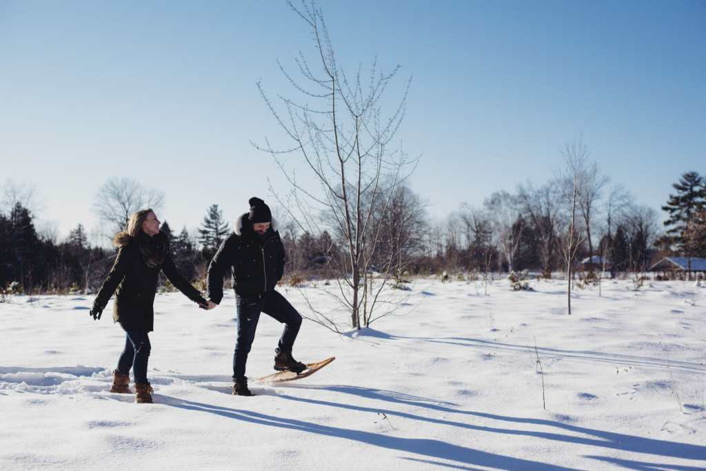 engaged couple snowshoeing in greenwood conservation area