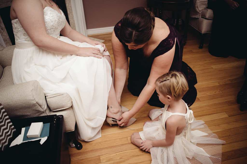 bridesmaid helps bride into her shoes at brooklin wedding
