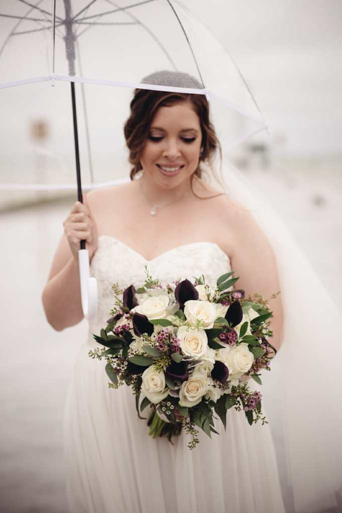 bride looks at her bridal bouquet in whitby wedding