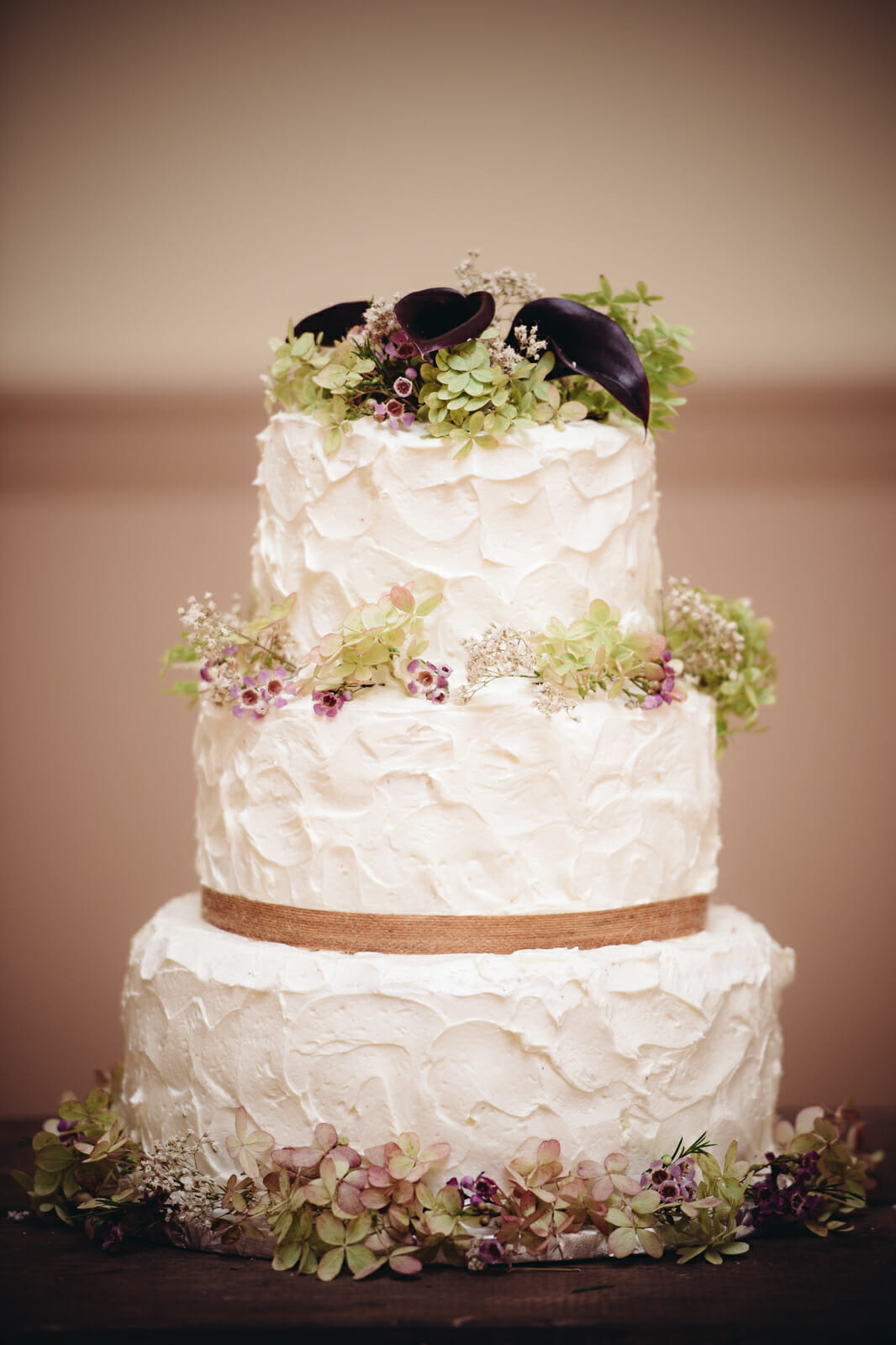 wedding cake with florals and wood