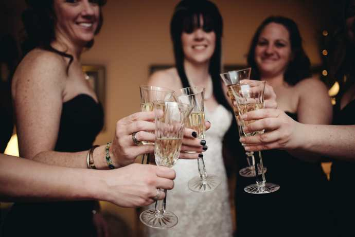 bride and bridesmaid champagne cheers before wedding