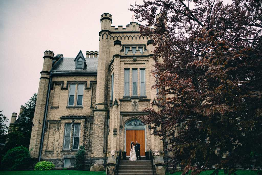 landscape photo of trafalgar castle school with bride and groom