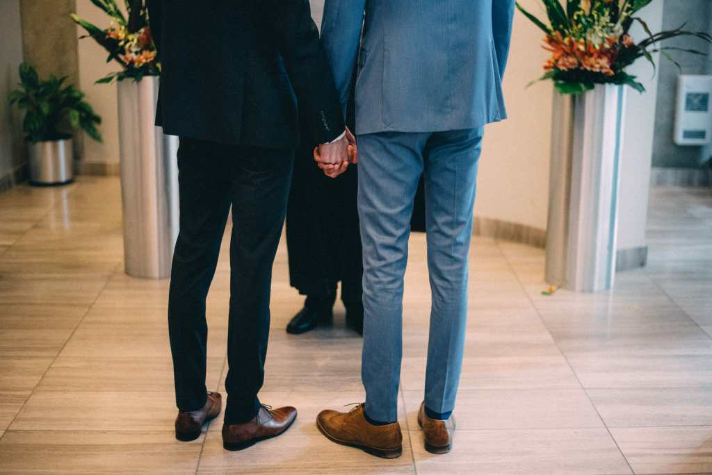 gay couple holding hands during ceremony
