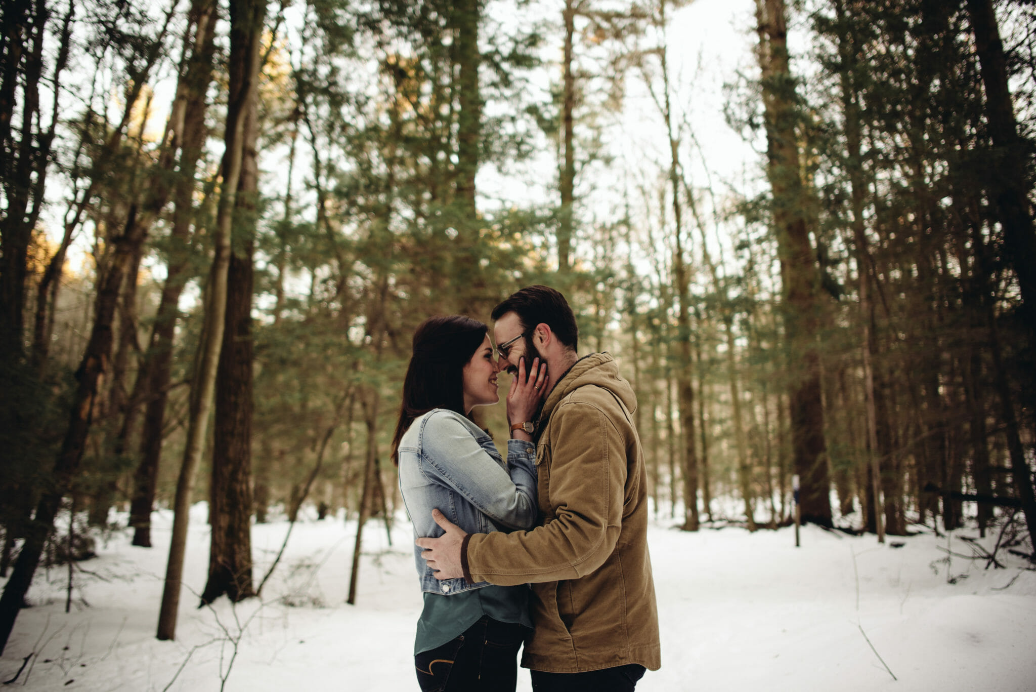 engaged couple laugh in the forest