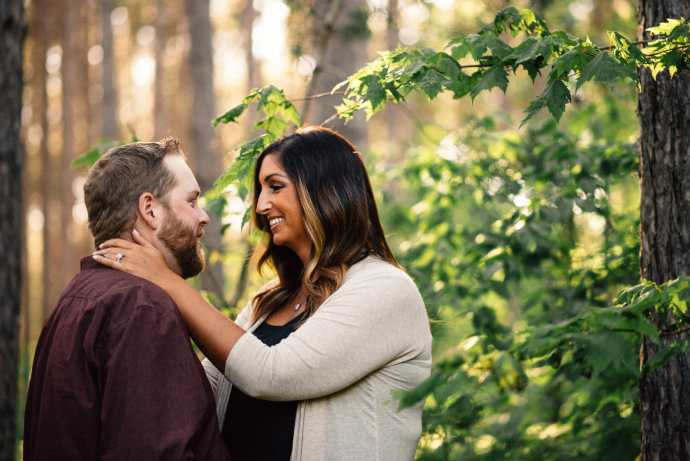 engaged couple embraces in forest