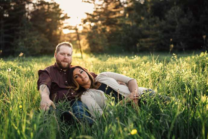 couple cuddling in tall grass during summer bowmanville engagement session